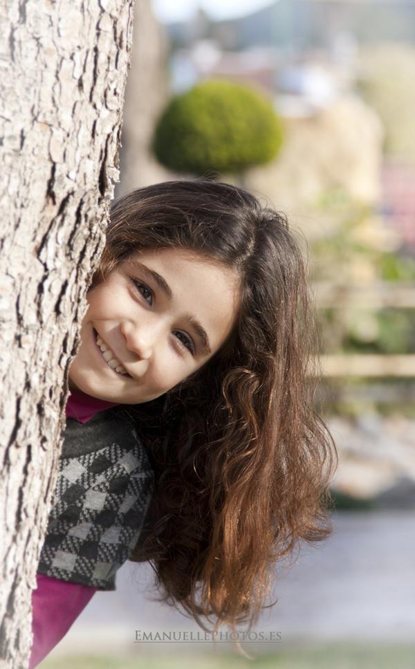 Simpática foto de niña asomándose detrás de un albero en Málaga