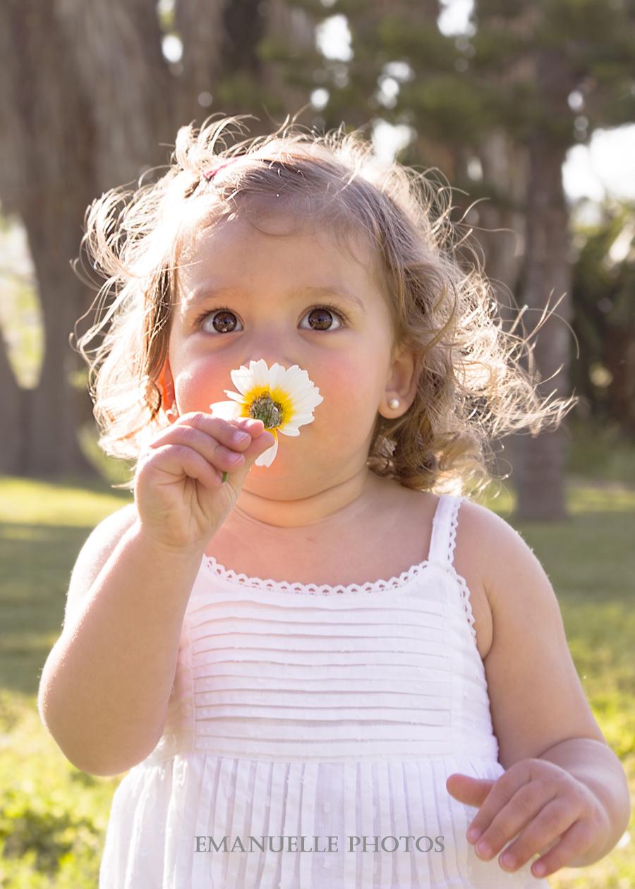 Foto de reportaje de niños oliendo una flor en málaga