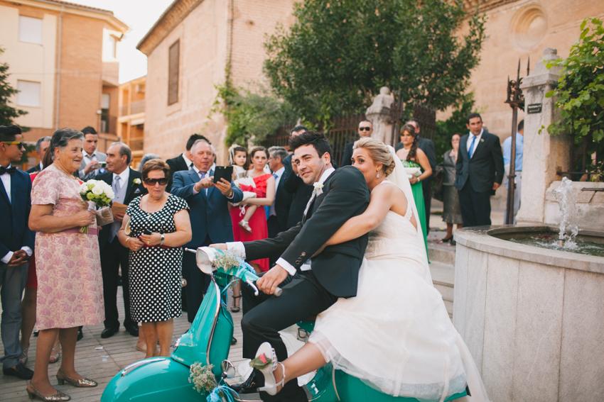los novios se divierten sobre la vespa utilizada para la boda