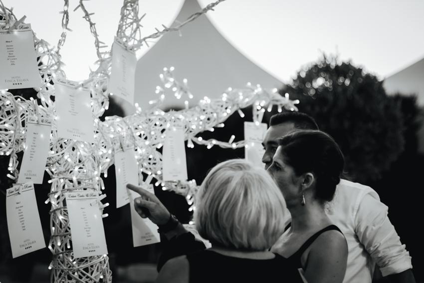 fotografía natural y espontanea de los invitado consultando la lista de mesas para sintarse