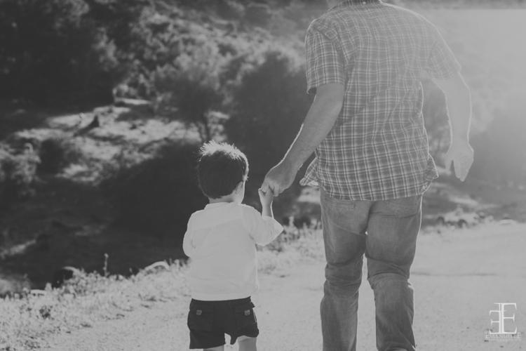 padre y niño paseando en el campo durante un reportaje de boda